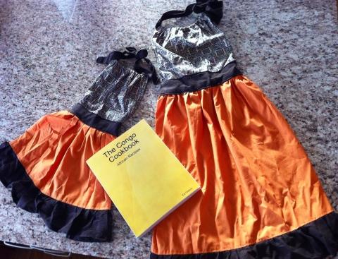 """A """"Me & Mini-Me"""" apron set and The Congo Cookbook."""